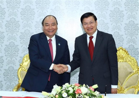 Prime Minister Nguyen Xuan Phuc (L) shakes hands with his Lao counterpart Thongloun Sisoulith at the inaugural ceremony of the Star Telecom's new headquarters